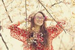 La muchacha adolescente en vidrios acerca al árbol del flor Imagen de archivo libre de regalías
