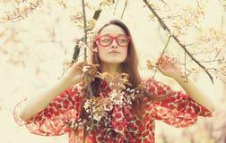 La muchacha adolescente en vidrios acerca al árbol del flor Imágenes de archivo libres de regalías