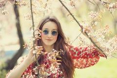 La muchacha adolescente en vidrios acerca al árbol del flor Fotografía de archivo