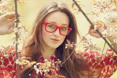 La muchacha adolescente en vidrios acerca al árbol del flor Fotos de archivo libres de regalías