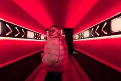 La muchacha adolescente en vidrios elegantes y la piel en luces de neón rosadas firman en la pared de la calle imagen de archivo