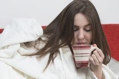 La muchacha adolescente enferma está bebiendo la taza caliente de té Fotos de archivo