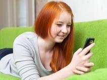 La muchacha adolescente envía SMS Imagen de archivo libre de regalías