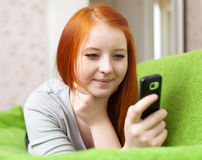 La muchacha adolescente envía SMS en móvil Imagen de archivo libre de regalías
