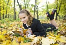 La muchacha adolescente escribe poesía en copybook en parque del otoño Fotografía de archivo