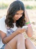 La muchacha adolescente escribe SMS en campo Fotos de archivo