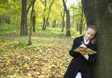 La muchacha adolescente escribe una poesía en parque del otoño Fotografía de archivo