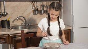 La muchacha adolescente está cocinando los ingredientes de mezcla de la pasta en un cuenco en cocina en casa almacen de video