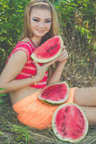 La muchacha adolescente está comiendo la sandía en parque verde Fotos de archivo libres de regalías