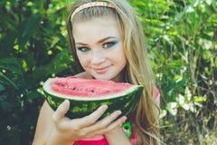 La muchacha adolescente está comiendo la sandía sobre hierba Foto de archivo