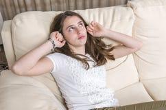 La muchacha adolescente está cubriendo su gesto de los oídos que se sienta en el sofá en casa Fotografía de archivo