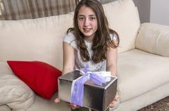 La muchacha adolescente está dando un regalo en casa Imagenes de archivo