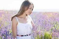 La muchacha adolescente está descansando sobre el campo púrpura de la lavanda Imagen de archivo