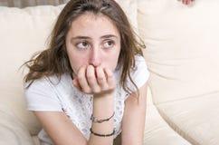 La muchacha adolescente está enojada en el sofá en casa Imagen de archivo