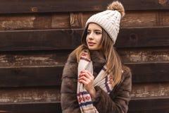 La muchacha adolescente está llevando el sombrero cerca de la pared de madera Fotos de archivo