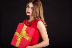 La muchacha adolescente está llevando el vestido rojo con la caja de regalo Imagen de archivo libre de regalías