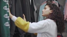 La muchacha adolescente está mirando las camisetas de moda en tienda con ropa de la juventud almacen de metraje de vídeo