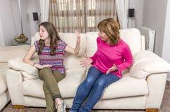 La muchacha adolescente está mostrando gesto de la parada a la madre enojada mientras que se sienta Foto de archivo libre de regalías
