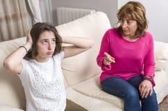 La muchacha adolescente está triste porque su madre está enojada en casa Imagenes de archivo