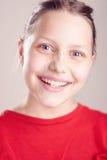 La muchacha adolescente feliz con friega la máscara en su cara Imagenes de archivo