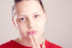 La muchacha adolescente feliz con friega la máscara en su cara Foto de archivo