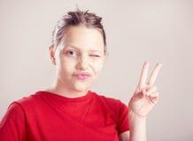 La muchacha adolescente feliz con friega la máscara en su cara Foto de archivo libre de regalías