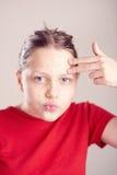 La muchacha adolescente feliz con friega la máscara en su cara Fotos de archivo