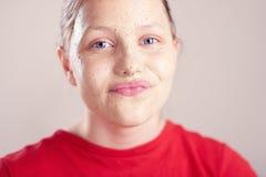 La muchacha adolescente feliz con friega la máscara en su cara Imagen de archivo libre de regalías
