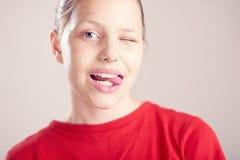 La muchacha adolescente feliz con friega la máscara en su cara Imágenes de archivo libres de regalías