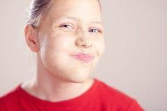 La muchacha adolescente feliz con friega la máscara en su cara Fotografía de archivo