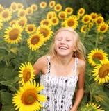 La muchacha adolescente feliz disfruta en el campo de girasoles Fotos de archivo libres de regalías