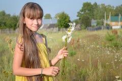 La muchacha adolescente feliz en el prado del verano, recogiendo florece Fotografía de archivo