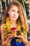 La muchacha adolescente feliz hermosa sostiene antes de sí mismo un regalo de la Navidad Imagen de archivo libre de regalías