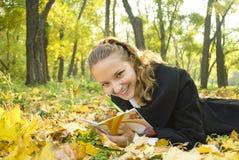 La muchacha adolescente feliz miente en el parque con su diario Fotografía de archivo