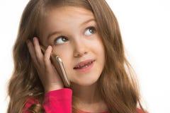 La muchacha adolescente feliz que se opone y que sonríe contra el fondo blanco Imagen de archivo libre de regalías