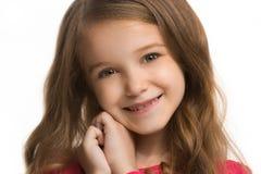 La muchacha adolescente feliz que se opone y que sonríe contra el fondo blanco Imágenes de archivo libres de regalías