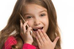 La muchacha adolescente feliz que se opone y que sonríe contra el fondo blanco Fotografía de archivo