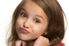 La muchacha adolescente feliz que se opone y que sonríe contra el fondo blanco Fotos de archivo