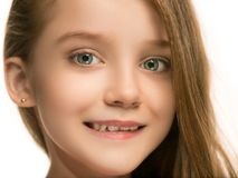 La muchacha adolescente feliz que se opone y que sonríe contra el fondo blanco Imagenes de archivo
