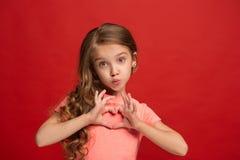 La muchacha adolescente feliz que se opone y que sonríe contra fondo rojo Foto de archivo