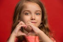 La muchacha adolescente feliz que se opone y que sonríe contra fondo rojo Imagenes de archivo