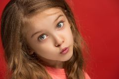 La muchacha adolescente feliz que se opone y que sonríe contra fondo rojo Foto de archivo libre de regalías
