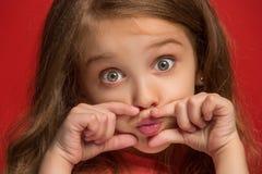 La muchacha adolescente feliz que se opone y que sonríe contra fondo rojo Imagen de archivo libre de regalías