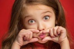 La muchacha adolescente feliz que se opone y que sonríe contra fondo rojo Fotografía de archivo
