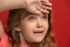 La muchacha adolescente feliz que se opone y que sonríe contra fondo rojo Fotografía de archivo libre de regalías