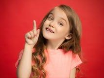 La muchacha adolescente feliz que se opone y que sonríe contra fondo rojo Imágenes de archivo libres de regalías