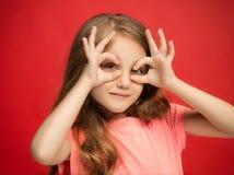La muchacha adolescente feliz que se opone y que sonríe contra fondo rojo Fotos de archivo libres de regalías
