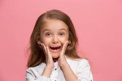 La muchacha adolescente feliz que se opone y que sonríe contra fondo rosado Imágenes de archivo libres de regalías