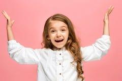 La muchacha adolescente feliz que se opone y que sonríe contra fondo rosado Imagenes de archivo