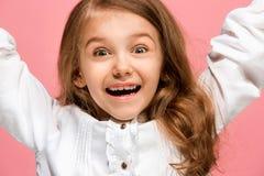 La muchacha adolescente feliz que se opone y que sonríe contra fondo rosado Fotografía de archivo libre de regalías